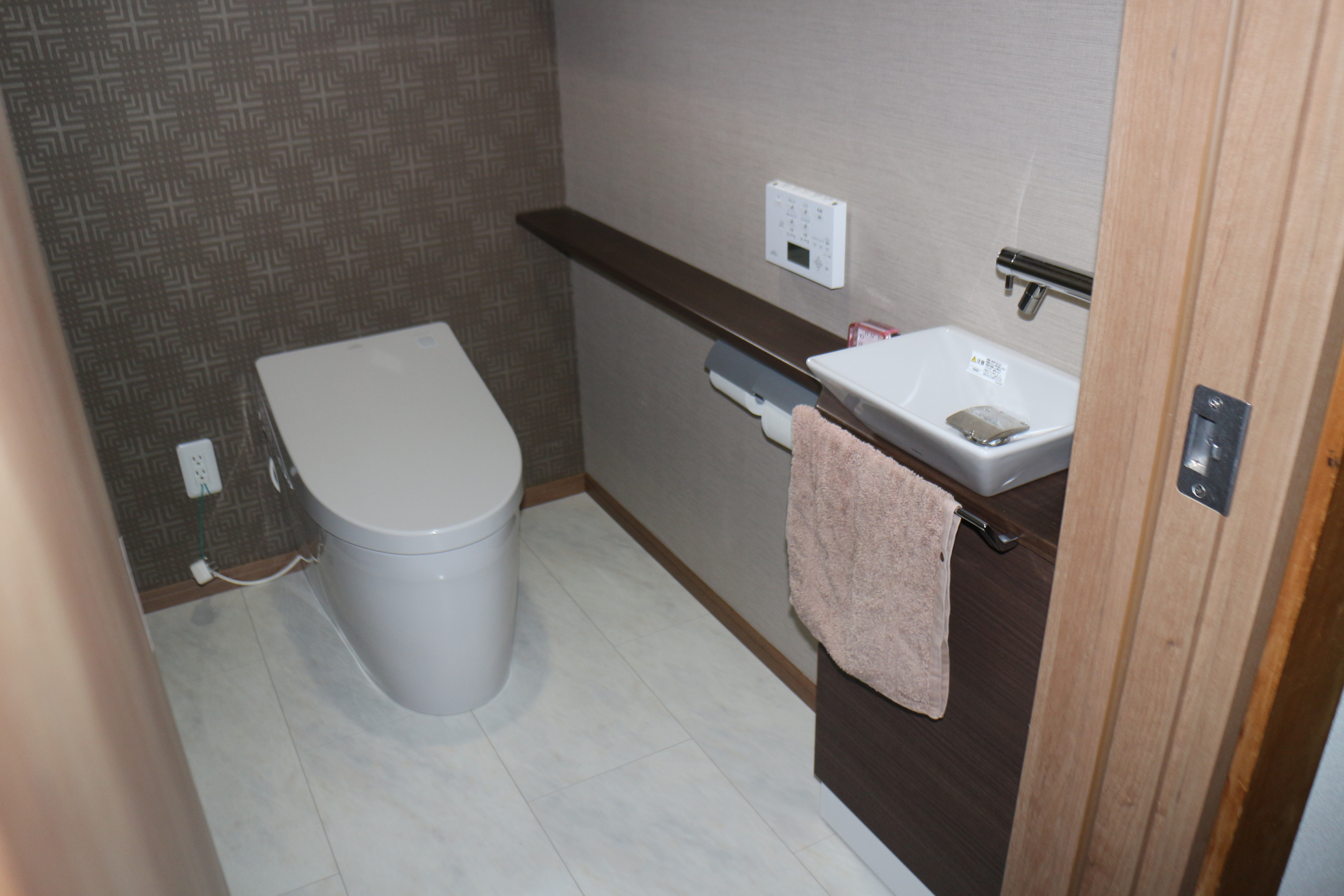 トイレ After<br> 壁紙にアクセントを持たせ、シックにまとまりました